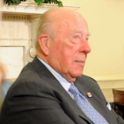Bild på två män i kostym och blå slipsar som sitter bredvid varandra och diskuterar.