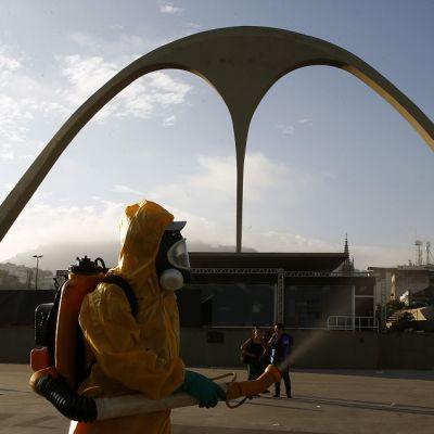 Keltaisiin suoja-asuihin ja kaasunaamareihin pukeutuneet ihmiset levittävät hyönteismyrkkyä selässä kannettavista säiliöistä. Paikka on Sambódromo, jossa pidetään paraateja sambakarnevaalien aikaan.