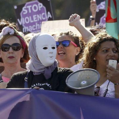 Joukko mielenosoitukseen osallistuneita naisia. Yhdellä on kasvoillaan naamio.