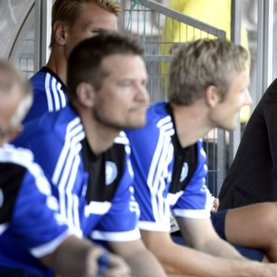 HJK-valmentaja Sixten Boström istuu huolestuneen näköisenä vaihtopenkin päässä.