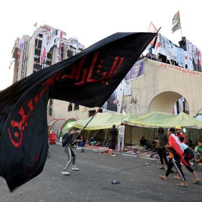Nuori mies heiluttaa kadulla suurta mustaa lippua, jossa on punaista arabiankielistä kirjoitusta.