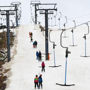 En snötäckt skidbacke med några personer som åker uppåt i en skidlyft.