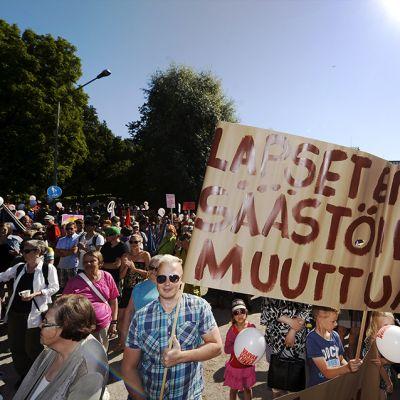 """Lapsia puolustava kyltti mielenosoituksessa hallituksen leikkauksia ja """"kurjistamispolitiikkaa"""" vastaan Helsingissä 22. elokuuta."""