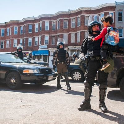 Mellakkavarusteisiin pukeutunut poliisi pitelee sylissään kolmivuotiasta pikkupoikaa.