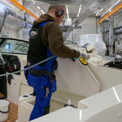 Työntekijä kiillottaa venettä Bellan Kuopion tehtaalla.