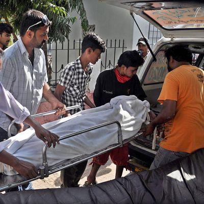 ruumista siirretään paareilla ambulanssiin