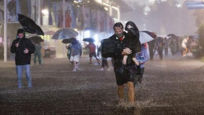 En man bär sitt barn genom en översvämmad parkeringsplats i New York.