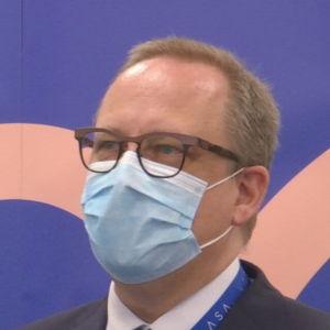 En man med munskydd och glasögon står framför en blå skärm.