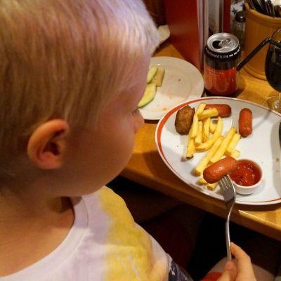 Barn äter barnportion på restaurang.