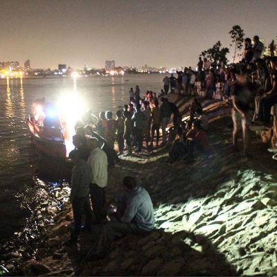 Ihmisiä on kokoontunut rannalle seuraamaan uhrien pelastusta öisestä Niilin virrasta.
