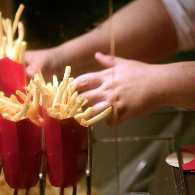 McDonald'sin työntekijä pakkaa ranskanperunoita.
