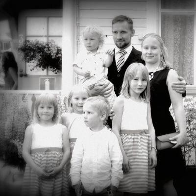 Tiina Timlin poseeraa perheensä kanssa sukujuhlissa.