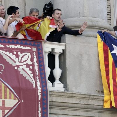 Katalonian alueparlamentin edustajat kiistelevät Barcelonan kaupungintalon parvekkeella lipuista torstaina 24.9. Kiista alkoi, kun itsenäisyysmieliset ripustivat parvekkeelle lippunsa ja espanjamieliset Espanjan lipun. Lopulta molemmat liput poistettiin parvekkeelta. Kuvassa toisella parveella kiihtyneet ihmiset irroittavat Espanjan lippua kaiteesta ja toisella parvekkeella parrakas mies levittää Katalonian lippua.
