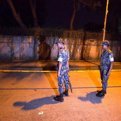 Bangladeshilaiset turvallisuusviranomaiset tarkkailevat Dhakan diplomaattialueella poliisinauhalla rajattua surmapaikkaa, missä italialainen avustustyöntekijä ammuttiin tiistaina 29. syyskuuta.
