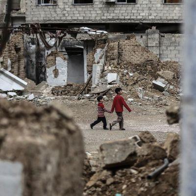 Kaksi lasta kävelee käsi kädessä raunioiden keskellä.