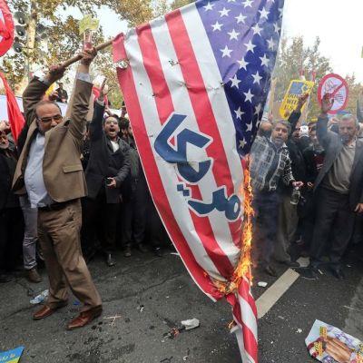 Mielenosoittaja nostaa palavaa Yhdysvaltain lippua. Taustalla suosiota osoittavia ihmisiä.