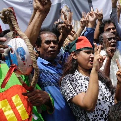 Väkijoukko näytttää sormillaan voitonmerkkejä.