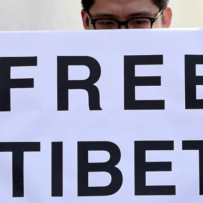 Silmälasipäinen mies pitelee edessään Free Tibet -kylttiä.