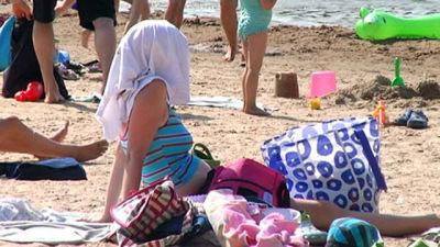 En massa personer på en badstrand en vacker sommardag.