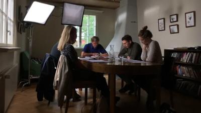 Regissören Claes Olsson och skådespelare sitter runt ett bord för manusgenomgång.