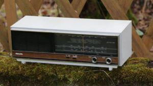 Vanha radio ulkona sammaleisen betonikorokkeen päällä.