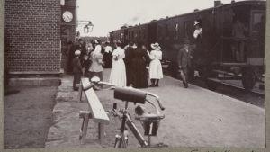 Människor vid ett tåg i svartvitt foto.