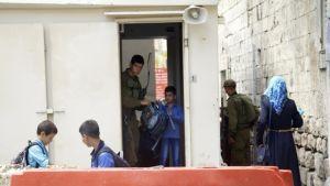 Soldat kontrollerar elevers skolväskor i Hebron