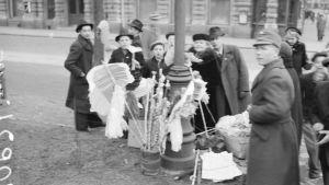 Barn som samlats på gatan runt en person som säljer majviskor.