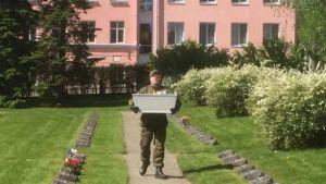 Kalle Multanens kista bärs av en representant från försvarsmakten.