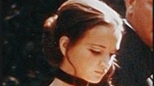 Närbild på skådespelaren Christina Lindberg som står i en svart urringad dräkt och läser en lapp.