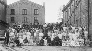 fabrikasarbetare på gruppbild på historiskt fotografi utanför Ensos fabrik