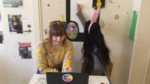 på bild Julia Grönvall,Emelie Elfving som ritar på ett papper som hänger på väggen.