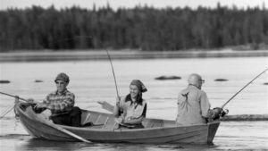 Gammal svartvit bild på en roddbåt och tre personen som sitter i båten och fiskar.