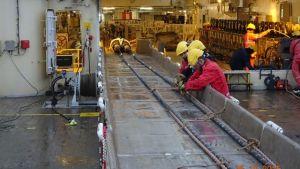 Arbetare jobbar med att sjösätta en kabel.