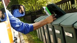 Postudelare lägger post i en postlåda.