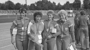 Fyra kvinnor i idrottskläder håller varandra om axlarna och ler mot kameran. Bilden är svartvit.