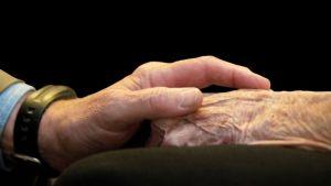 äldre par håller handen