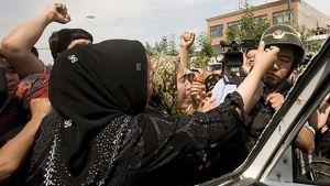 Uigurkvinna knuffar polis under protesterna i Xinjiang 7.7.2009.