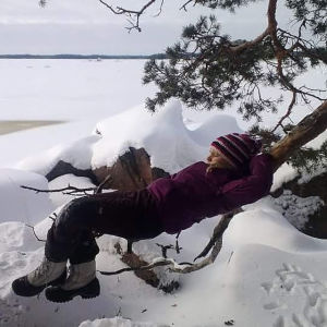 Lapsi makaa puunrungolla.
