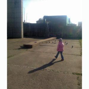 tyttö kävelee betonimaisemassa prahassa
