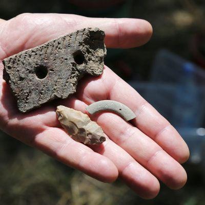 Kädessä on arkeologisia löytöjä.