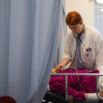 Amanuenssi Annika Ström kuuntelee naisen rintakehää stetoskoopilla.