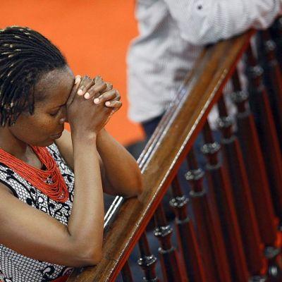 nainen rukoilee kirkossa nojaten kaiteeseen