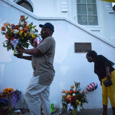 Ihmiset tuovat Charlestonin joukkosurman tapahtumapaikalle.