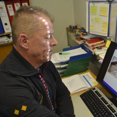 Esa Koskinen katsoo kuvia öljysäiliöstä tietokoneeltaan.