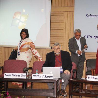 """""""Etiikka, Tiede ja Kasvatus"""" -konferenssi Delhin Yliopistossa. Neurotieteilijät Nandini Chatterjee-Singh ja Clifford Saron lavalla Dalai-laman kanssa."""