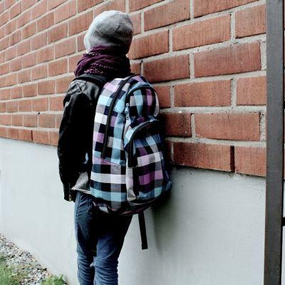 Koululainen nojaa koulun seinään.
