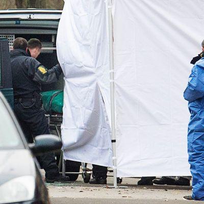 Poliisi siirtää ruumista autoon.