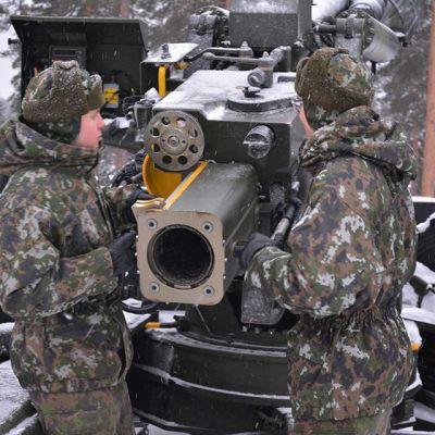 Sotilaat lataavat ammusta tykkiin.