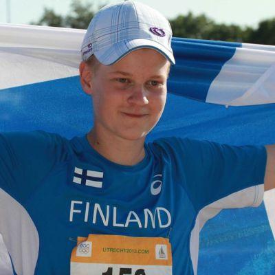 Jyri Isokääntä poseeraa Suomen lipun kanssa.